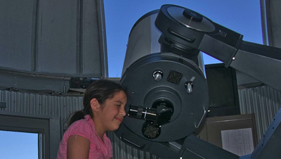 Girl looking through telescope during lunar viewing.
