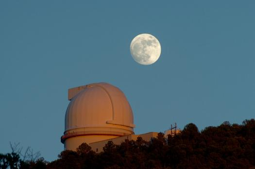 A nearly full gibbous Moon shines at sunset over the dome of the 2.7-meter (107-