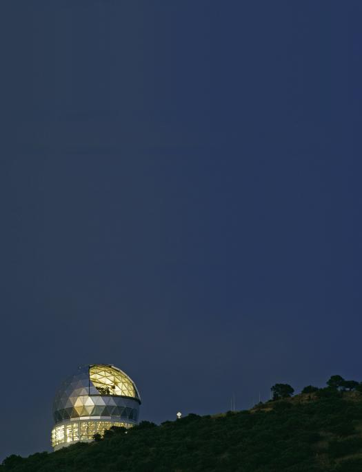 The Hobby-Eberly Telescope gleams in silver and gold against a deep blue night s