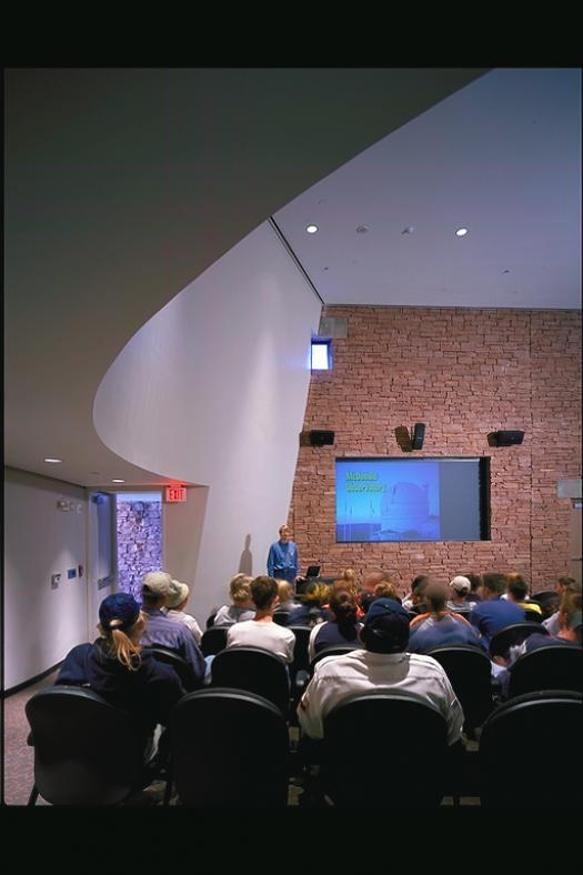 Visitors watch an orientation presentation.